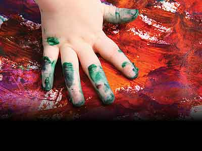 A child's hand making a finger painting