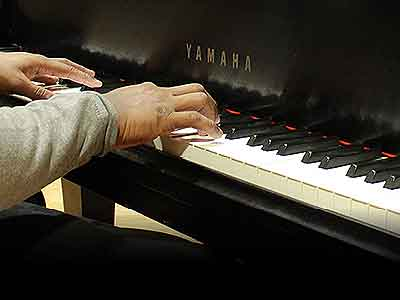 Student playing a piano