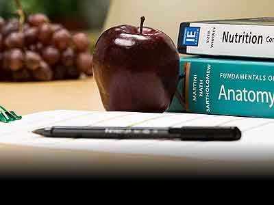 Nutrition and anatomy textbooks with fruit next to them