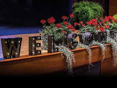 A stage featuring a welcome sign and flowers