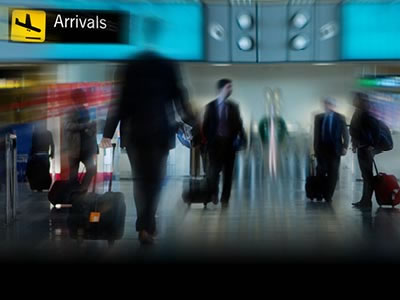 People walking through airport with luggage
