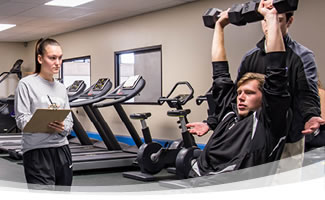 Three students in the FLCC Fitness Center. One student is documenting a student participant as he lifts free weights